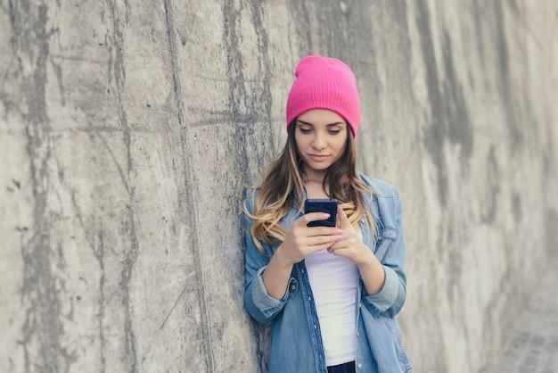 Mädchen in der rosa kopfbedeckung, die gegen wand hält, die smartphone hält