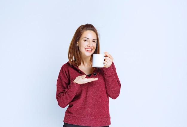 Mädchen in der roten jacke, die eine weiße kaffeetasse hält und das produkt riecht.