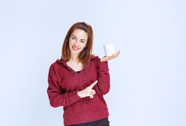 Mädchen in der roten jacke, die eine weiße kaffeetasse hält.