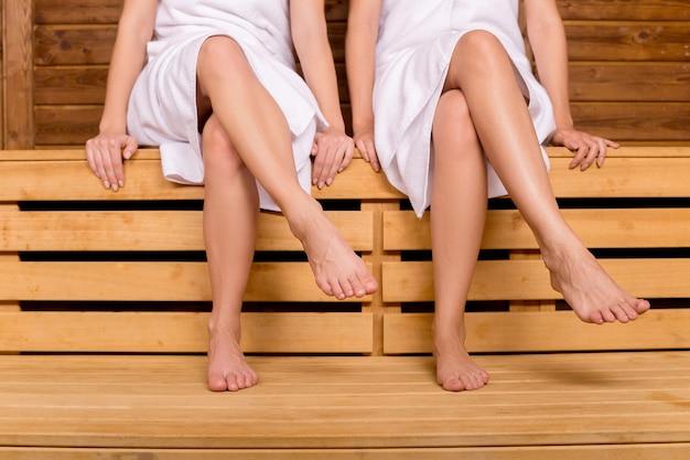 Mädchen in der sauna. abgeschnittenes bild von weiblichen beinen in der sauna