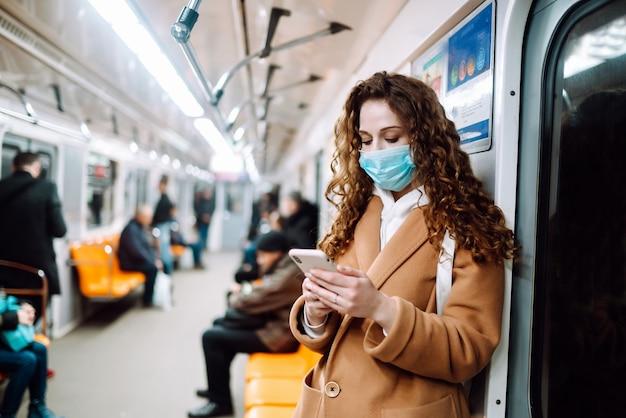 Mädchen in der schützenden sterilen medizinischen maske auf ihrem gesicht mit einem telefon in einem u-bahnwagen. frau, die das telefon benutzt, um nach nachrichten über coronavirus zu suchen. das konzept, die ausbreitung der epidemie zu verhindern.