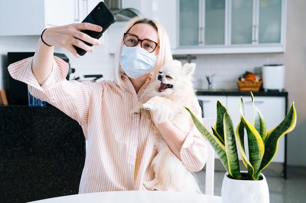 Mädchen in der schutzmaske, die zu hause sitzt und videoanruf hält.