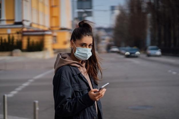 Mädchen in der schutzmaske unter verwendung des smartphones im freien. covid 19. weltkoronavirus-pandemie.