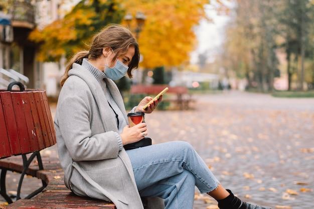 Mädchen in der schutzmaske unter verwendung des telefons im park. technologiekonzept