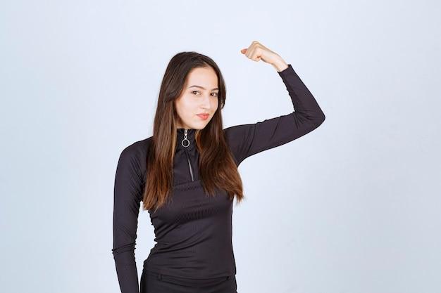 Mädchen in der schwarzen kleidung, die ihre faust- und armmuskeln zeigt.