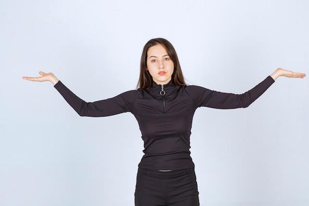 Mädchen in der schwarzen kleidung, die meditation tut.