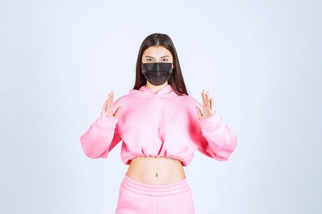 Mädchen in der schwarzen maske, die die menge oder größe eines produktes zeigt.