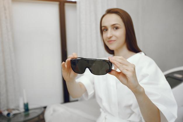 Mädchen in der sicherheitsbrille, die in einem kosmetikstudio sitzt
