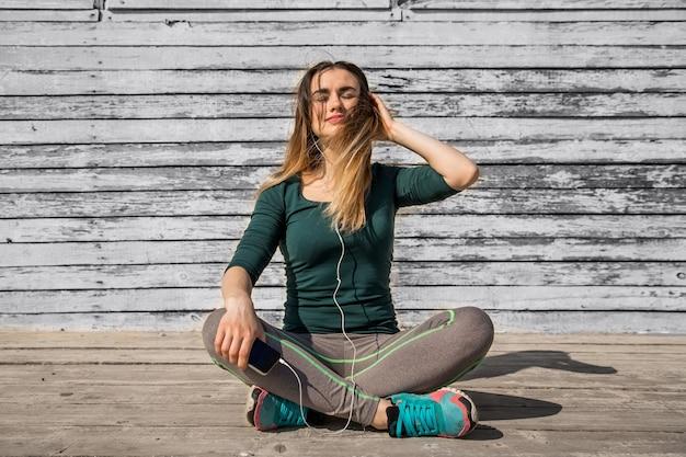 Mädchen in der sportbekleidung, die musik, sportmotivation, sport, fitness, fitnessmädchen hört, das auf hölzernem hintergrund sitzt