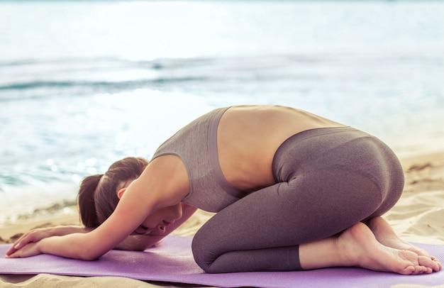 Mädchen in der sportkleidung, die auf yogamatte auf dem strand ausdehnt.