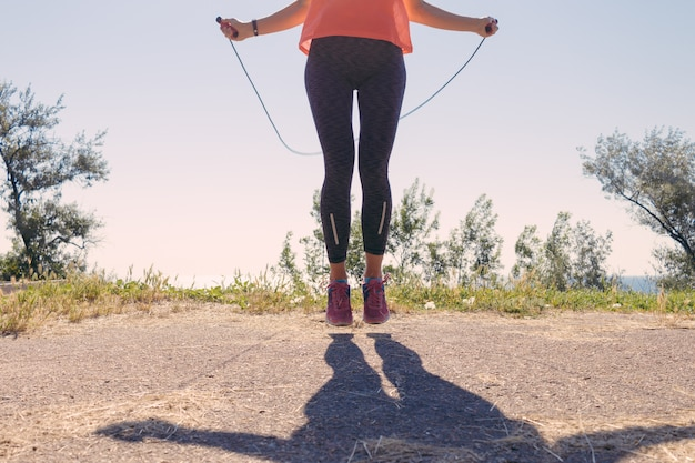 Mädchen in der sportkleidung und in turnschuhen, die an mit einem springseil im sommer des seehintergrundes springen
