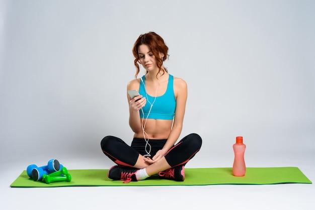 Mädchen in der sportkleidung untersucht das telefon.