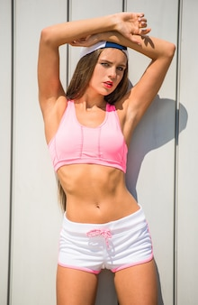 Mädchen in der sportkleidung wirft gegen die wand auf, die im freien ist.