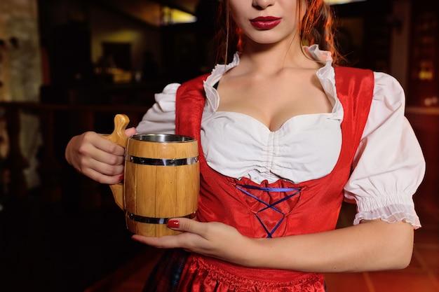 Mädchen in der traditionellen bayerischen kleidung mit einem hölzernen becher bier auf dem hintergrund der kneipe während der feier von oktoberfest