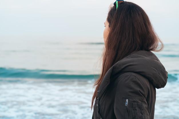 Mädchen in der warmen jacke, die das meer beim auf den strand im frühjahr gehen betrachtet