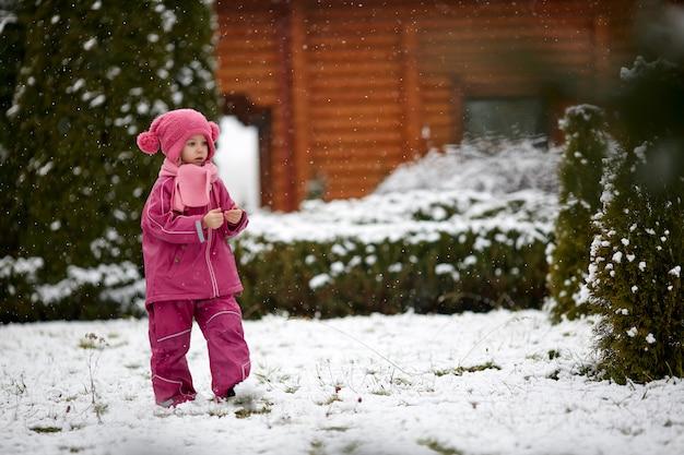 Mädchen in der warmen oberbekleidung, die auf schnee geht