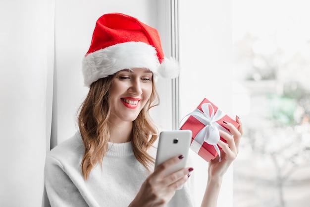 Mädchen in der weihnachtsmütze, die geschenkbox hält