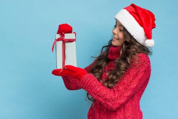 Mädchen in der winterkleidung, die ihr geschenk betrachtet