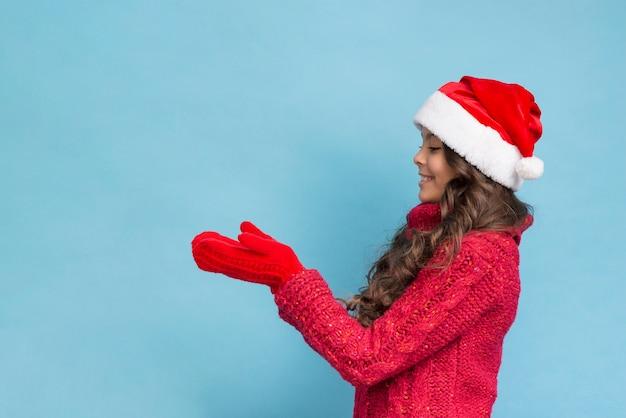 Mädchen in der winterkleidung, die ihre handschuhe betrachtet