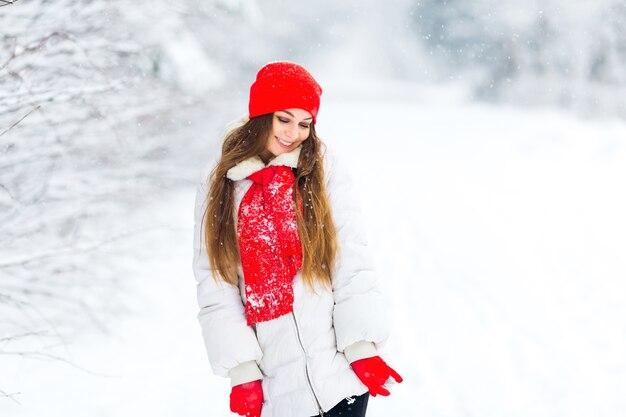 Mädchen in der winterkleidung und im roten hut wirft in einem verschneiten park auf