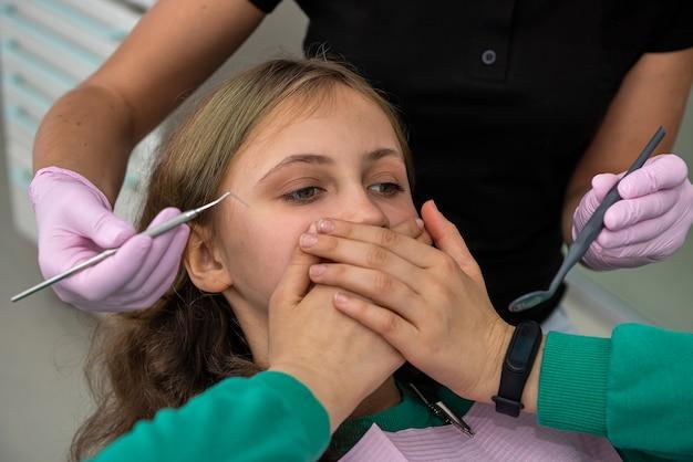 Mädchen in der zahnarztpraxis schließt mit den händen den mund und lässt die erstuntersuchung nicht zu