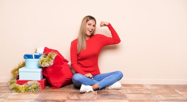 Mädchen in die weihnachtsfeiertage, die auf dem boden bildet starke geste sitzen