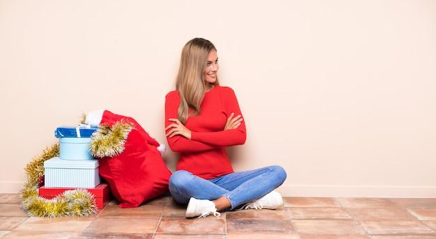 Mädchen in die weihnachtsfeiertage, die auf dem boden schaut zur seite sitzen