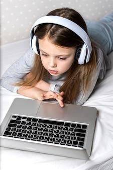 Mädchen in drahtlosen kopfhörern mit laptop zu hause für online-bildung und fernunterricht