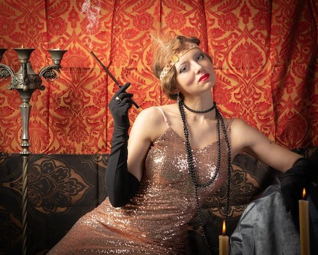 Mädchen in einem abendkleid mit einer zigarette. studiofoto im retro-stil studio