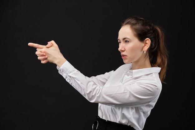 Mädchen in einem abstrakten weißen hemd, das eine waffe aus den händen auf einem schwarzen hintergrund zielt.