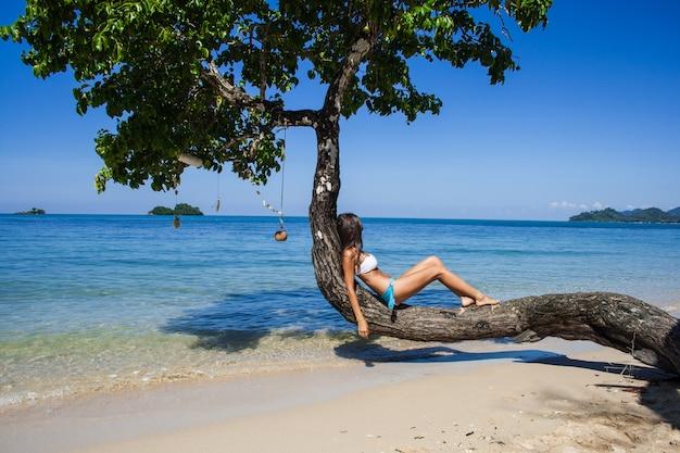 Mädchen in einem badeanzug am strand ausruhen und das meer betrachten
