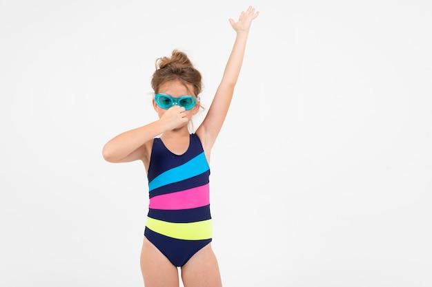 Mädchen in einem badeanzug mit brille zum tauchen unter wasser auf einem weißen