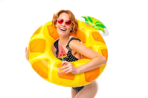 Mädchen in einem badeanzug mit einem lutscher legte auf einen kreis zum schwimmen