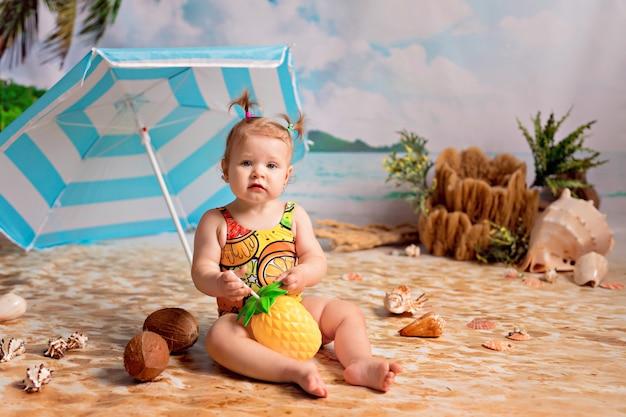 Mädchen in einem badeanzug nimmt ein sonnenbad auf einem sandstrand mit palmen am meer unter einem sonnenschirm
