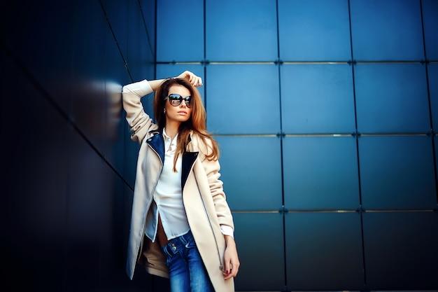 Mädchen in einem beige mantel und in der blue jeans