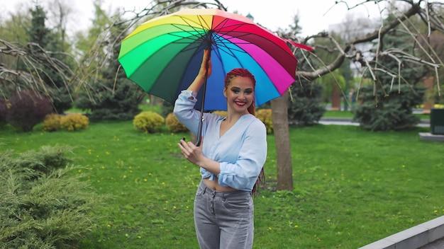 Mädchen in einem bläulichen hemd mit hellem make-up und langen farbigen zöpfen. halten sie einen regenschirm in den farben des regenbogens auf einem blühenden park und genießen sie den kommenden frühling