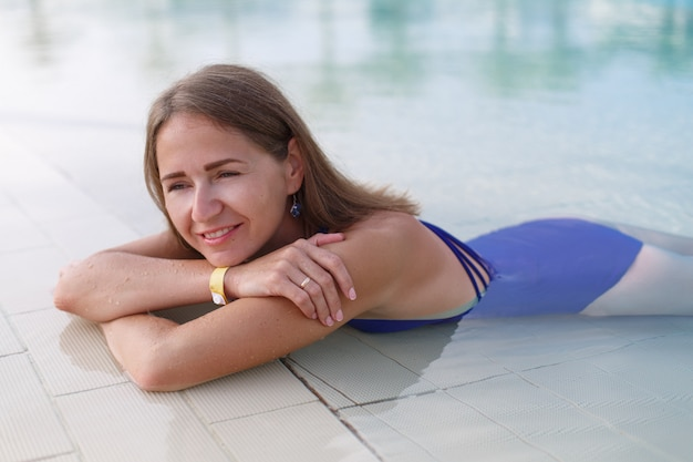 Mädchen in einem blauen badeanzug am pool. schlanke blondine schwimmt im pool.