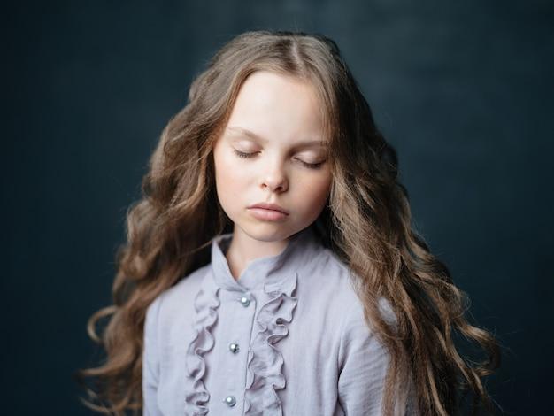 Mädchen in einem blauen kleid auf einem dunklen hintergrund und lockigem abgeschnittenem haar. hochwertiges foto