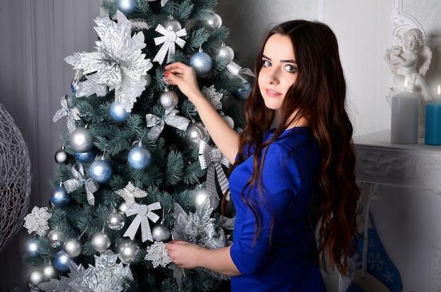 Mädchen in einem blauen kleid schmückt einen weihnachtsbaum