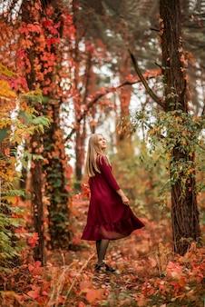 Mädchen in einem burgunderroten kleid geht in den herbstlichen wald. ein fabelhafter wald mit einem wilden weinberg..