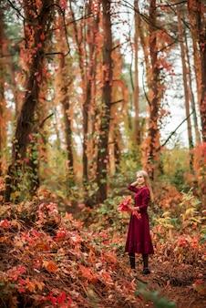 Mädchen in einem burgunderroten kleid geht in den herbstlichen wald. schöner wald mit hohen bunten bäumen.