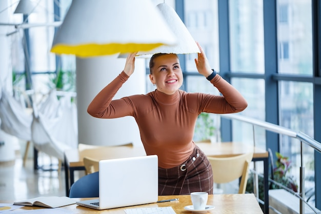 Mädchen in einem café steht an einem holztisch und lächelt und albert mit kaffee herum und spielt mit einer lampe