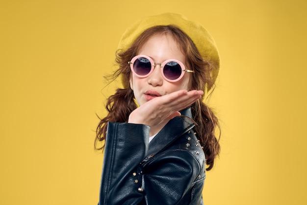 Mädchen in einem gelben hut dunkle brille modische kleidung studio lebensstil kindheit.