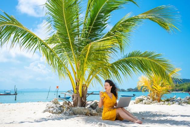 Mädchen in einem gelben kleid an einem tropischen sandstrand arbeitet an einem laptop und trinkt frische mango. fernarbeit, erfolgreiche freiberufliche tätigkeit. arbeitet im urlaub.