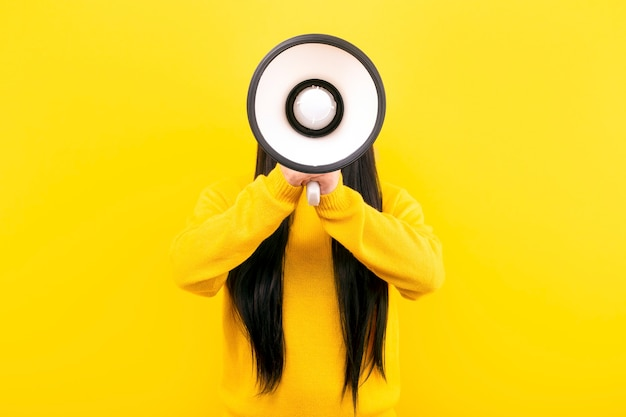 Mädchen in einem gelben pullover mit einem megaphon