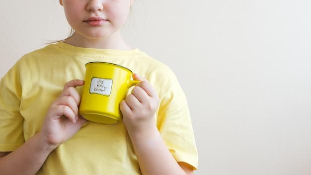 Mädchen in einem gelben t-shirt mit einem gelben becher in ihrer hand