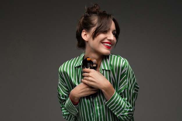 Mädchen in einem gestreiften hemd hält make-up-pinsel an einer dunklen wand
