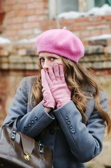 Mädchen in einem grauen mantel und einer rosa baskenmütze, bedeckt ihr gesicht mit ihren händen