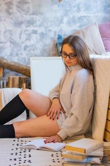 Mädchen in einem grauen sweatshirt, das unten mit brille und buch sitzt