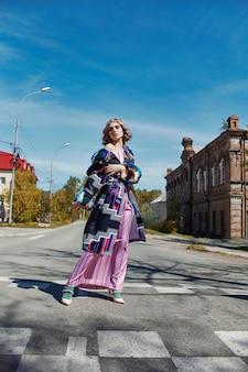 Mädchen in einem handgemachten kleid der ethnischen mode der weinlese, das draußen aufwirft. ungewöhnliches retro kostüm auf mädchenkörper